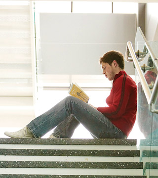 Male student reading book on stairs.